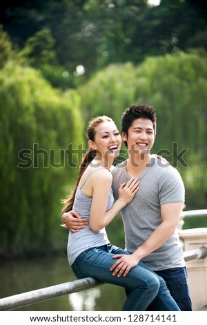 Attractive Asian Couple happy in park - stock photo