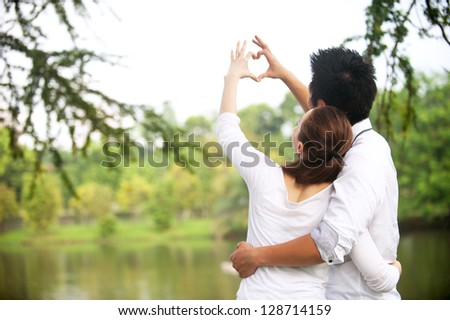 Attractive Asian Couple making a love symbol with hands - stock photo