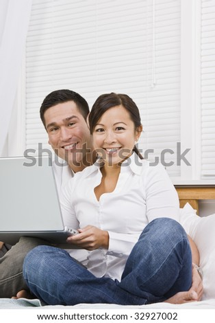 Attractive Asian couple sitting together with laptop. Vertically framed shot. - stock photo