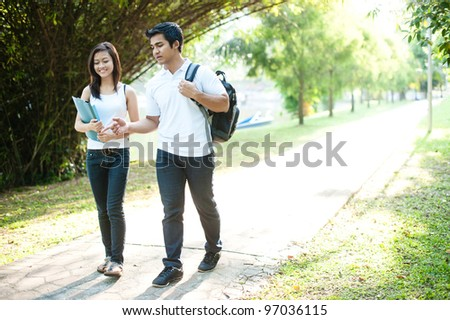 Attractive asian couple spending time together in the park - stock photo