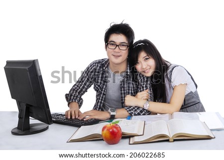Attractive asian couple spending time together while studying, isolated on white - stock photo