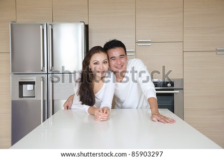 Attractive Asian Couple standing close to each other in the kitchen - stock photo