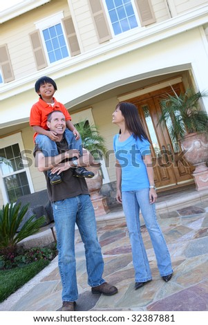 Attractive asian family outside their home having fun - stock photo