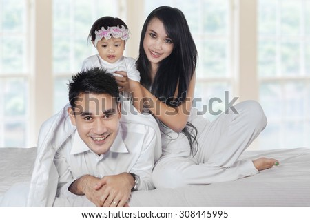 Attractive asian family playing together in the bedroom, smiling at camera - stock photo