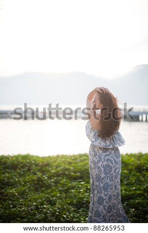 Attractive asian female staring out at the sea - stock photo