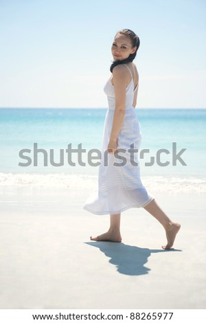 Attractive Asian female walking on the beach looking at the camera - stock photo