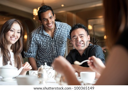 Attractive Asian Friends in Restaurant - stock photo