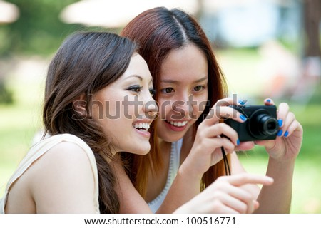 Attractive Asian Friends using a camera - stock photo