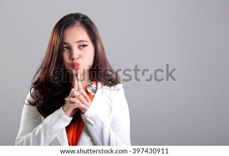 Attractive Asian girl in white suit making cute face while looking at empty space on her side - stock photo