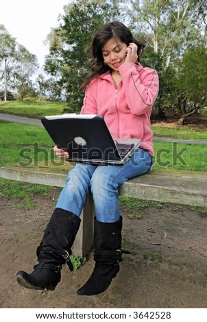 Attractive asian girl talking on a phone and using laptop - stock photo