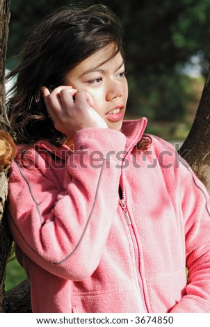 Attractive asian girl talking on her cell phone - stock photo