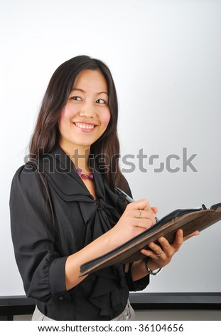 Attractive Asian girl writing in her notepad and smiling - stock photo