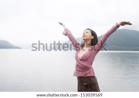 Attractive asian japanese young woman standing by a lake and mountains with her arms raised up under the rain during a cold and stormy day. In tune with nature, outdoors. - stock photo