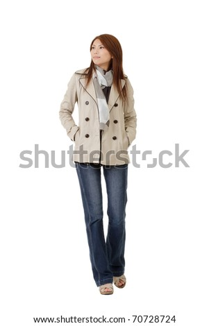 Attractive Asian lady with coat walking on studio white background. - stock photo