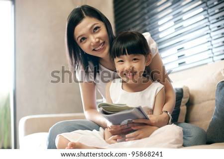 Attractive asian mother reading with her daughter - stock photo