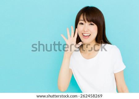 attractive asian nurse on blue background - stock photo