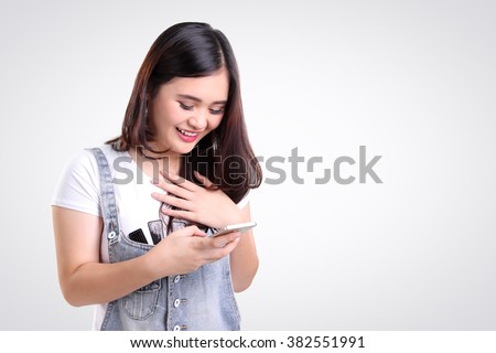 Attractive Asian teenage girl looking at her mobile phone screen with joyful face, on white background for copy space - stock photo