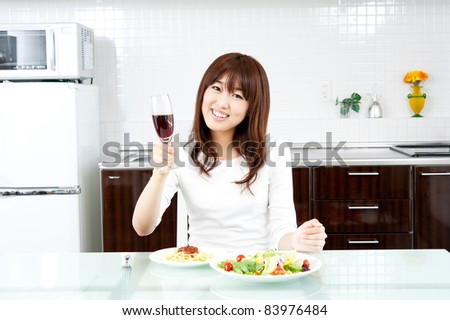 attractive asian woman eating in the kitchen