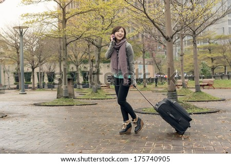 Attractive Asian woman holding suitcase and talking on phone at street, Taipei, Taiwan. - stock photo