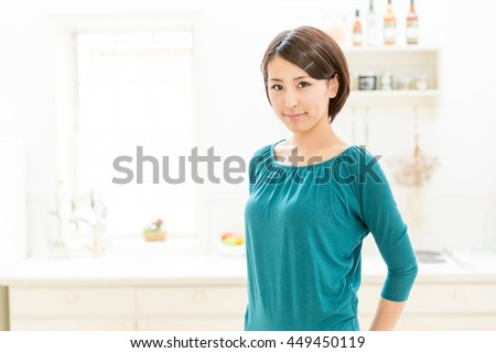 attractive asian woman in the kitchen - stock photo