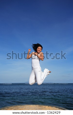 Attractive asian woman jumping on a beach - stock photo