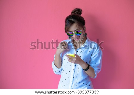 attractive asian woman listening music in Smart Phone on Pink background