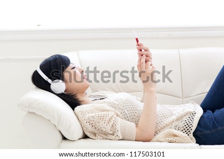 attractive asian woman listening music on the sofa