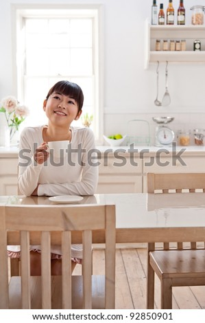 attractive asian woman relaxing in the kitchen - stock photo