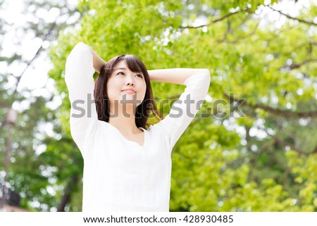 attractive asian woman relaxing in the park