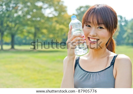 attractive asian woman relaxing in the park - stock photo