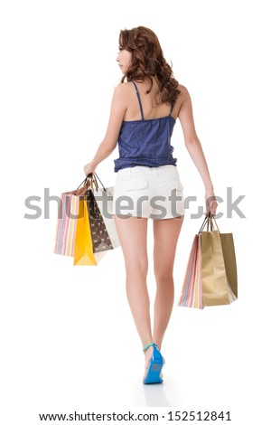Attractive asian woman shopping and holding bags. Full length portrait. Rear view. Isolated on the white background.