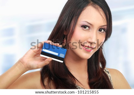 attractive asian woman showing  credit card for shopping - stock photo
