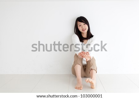 attractive asian woman sitting on the floor - stock photo