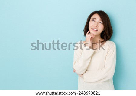 attractive asian woman thinking isolated on blue background - stock photo
