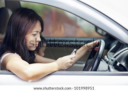 Attractive asian woman using a mobile phone while driving