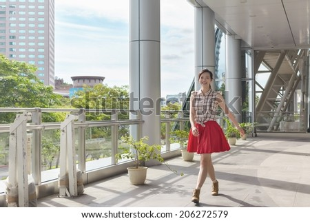 Attractive Asian woman walking in the city. - stock photo