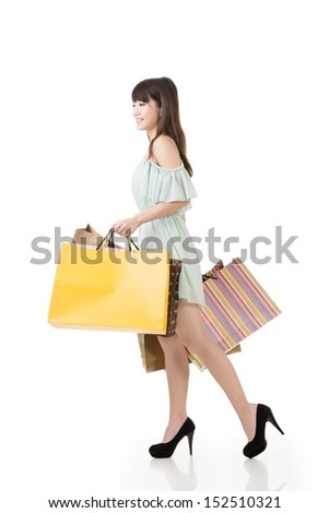 Attractive asian woman walking with shopping bags. Profile view. Portrait isolated on the white background. - stock photo