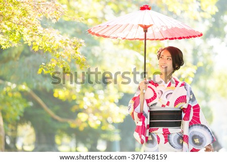 attractive asian woman wearing kimono walking in the park