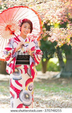 attractive asian woman wearing kimono walking in the park - stock photo
