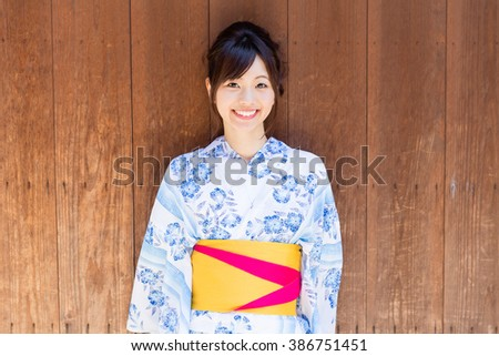 attractive asian woman wearing kimono walking on the old street - stock photo