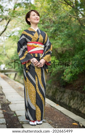 attractive asian woman wearing traditional Japanese kimono - stock photo