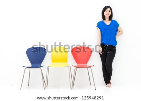 attractive asian woman with colorful chairs on white background