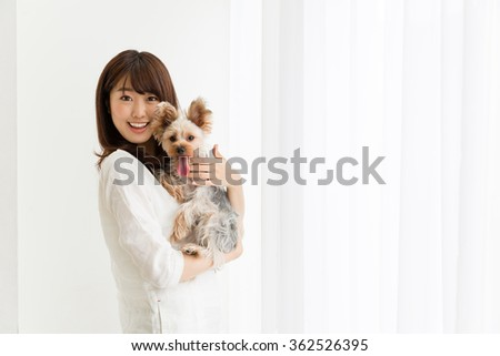 attractive asian woman with dog in the room - stock photo