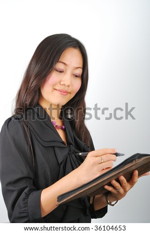 Attractive Asian woman writing something in her personal organizer - stock photo