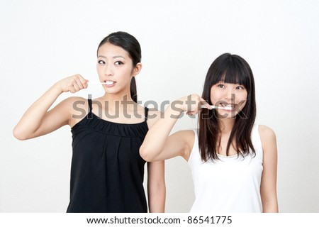 attractive asian women brushing her teeth - stock photo