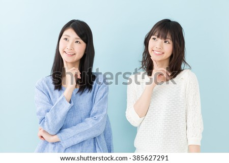 attractive asian women on blue background - stock photo