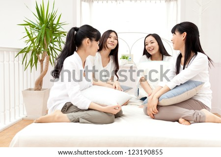 attractive asian women relaxing in the bed room - stock photo