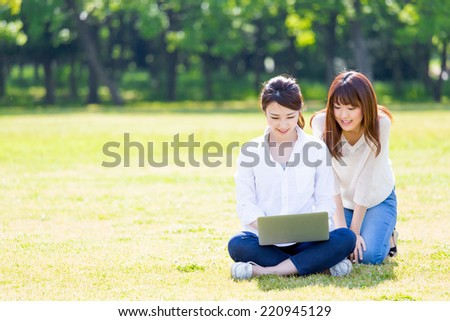 attractive asian women using laptop in the park - stock photo