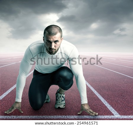 Attractive athlete on a race track is ready to run - stock photo