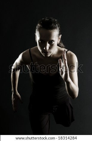 attractive athlete running over black background